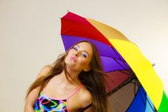 Het gelukkige vrouw stellen in zwempak en kleurrijke paraplu stock afbeelding