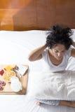 Het gelukkige vrouw uitrekken en zich wat betreft haar haar op het bed met bre Stock Fotografie