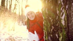 Het gelukkige vrouw verbergen achter grote boom in de winterpark en het werpen van sneeuwbal in camera in langzame motie stock videobeelden