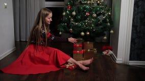 Het gelukkige vrouw zetten stelt onder Kerstboom voor stock video