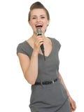 Het gelukkige vrouw zingen in geïsoleerdee microfoon Royalty-vrije Stock Foto's