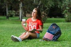 Het gelukkige vrouwelijke toerist ontspannen in park royalty-vrije stock afbeelding