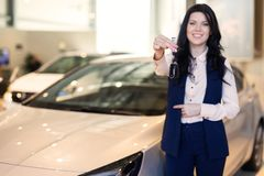 Het gelukkige vrouwenkoper possing met sleutels dichtbij haar nieuw voertuig in het autohandel drijven royalty-vrije stock afbeelding