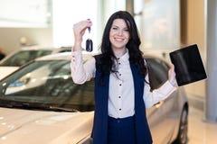 Het gelukkige vrouwenkoper possing met sleutels dichtbij haar nieuw voertuig in het autohandel drijven stock afbeelding