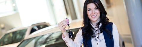 Het gelukkige vrouwenkoper possing met sleutels dichtbij haar nieuw voertuig in het autohandel drijven stock afbeeldingen