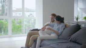 Het gelukkige Wachten van baby, jonge vrouw met zenuwen vertelt man over zwangerschap en zet wapens op buik en toekomstige papagl stock video