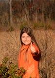 Het gelukkige wandelende meisje die duimen tonen ondertekent omhoog Stock Afbeelding
