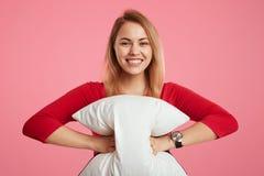 Het gelukkige wijfje houdt hoofdkussen, heeft gezonde droom, blij om nieuwe dag te beginnen, draagt rode sweater, stelt tegen roz royalty-vrije stock foto