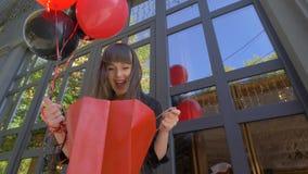 Het gelukkige winkelen, jong meisje kijkt verbaasd in giftzak en glimlacht gelukkig tegen een zwarte achtergrond met ballons stock videobeelden