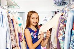 Het gelukkige zoeken naar kleren op hangers in opslag Royalty-vrije Stock Foto