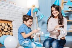Het gelukkige zoon spelen met stuk speelgoed robots met zijn moeder Royalty-vrije Stock Afbeelding