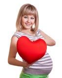 Het gelukkige zwangere rode hart van de vrouwengreep in handen stock afbeelding