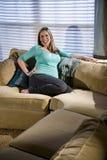Het gelukkige zwangere vrouw ontspannen op bank stock fotografie