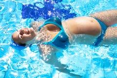 Het gelukkige zwangere vrouw swwing in zwembad Royalty-vrije Stock Afbeeldingen