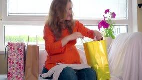 Het gelukkige zwangere wijfje na het winkelen zitting op bank en bekijkt babykleren stock footage