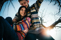 Het gelukpaar omhelst De jonge mens koestert meisje op boomtak royalty-vrije stock afbeeldingen