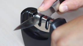 Het gemakkelijke het mes van de close-upkeuken scherpen door speciale drie-stappen messenslijper stock videobeelden
