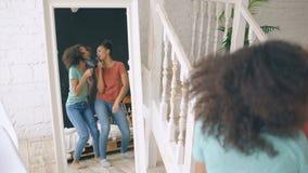Het gemengde de dans van ras jonge grappige meisjes zingen met hairdryer en kam voor spiegel Zusters die pretvrije tijd hebben bi stock video