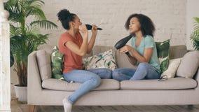 Het gemengde de dans van ras jonge grappige meisjes zingen met hairdryer en kamzitting op bank Zusters die pretvrije tijd in het  stock video