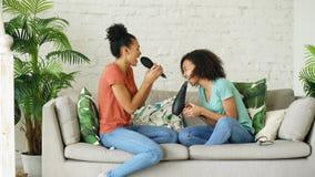 Het gemengde de dans van ras jonge grappige meisjes zingen met hairdryer en kamzitting op bank Zusters die pretvrije tijd in het  Royalty-vrije Stock Afbeeldingen