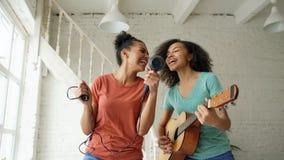 Het gemengde de dans van ras jonge grappige meisjes zingen met hairdryer en het spelen akoestische gitaar op een bed Zusters die  Stock Foto