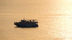 Het gemiddelde cruisepassagiersschip die op het overzees bij zonsondergang varen Silhouetten van mensen op het schip stock footage