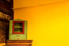 Het geneeskundekabinet van hout en pleistermuur schilderde geel stock foto's