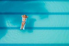 Het genieten van van bruine kleur Het concept van de vakantie Hoogste mening van slanke jonge vrouw in bikini op de blauwe luchtm stock afbeelding