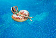 Het genieten van bruine kleur van Vrouw in bikini op de opblaasbare matras stock fotografie