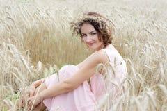 Het genieten van de van Aard Vrouwenzitting in het vooraanzicht van het tarwegebied stock foto