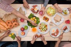 Het genieten van van diner met vrienden Hoogste mening van groeps mensen havin stock fotografie