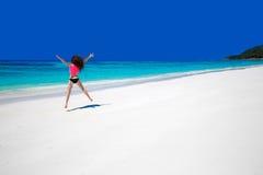 Het genieten van het van leven Gelukkige vrouw die op exotische overzees springen Geschikt donkerbruin g Stock Foto's
