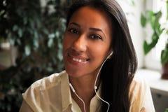 Het genieten van van muziek Aantrekkelijke jonge Afrikaanse vrouw die hoofdtelefoons dragen Royalty-vrije Stock Foto