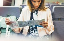Het genieten van van reis Het jonge meisje van de hipsterglimlach met rugzak die door treinzitting dichtbij de in hand vensterhol royalty-vrije stock foto