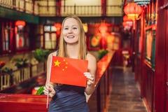 Het genieten van van vakantie in China Jonge vrouw met een Chinese vlag op een Chinese achtergrond Reis naar het concept van Chin stock afbeeldingen
