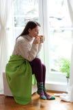 Het genieten van van thee door het venster Royalty-vrije Stock Afbeeldingen