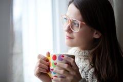 Het genieten van van thee door het venster Stock Afbeelding