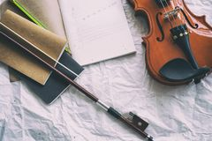Het geopende boek met tekeningsnota gezet bij het midden van halve voorkant van viool en boog stock fotografie
