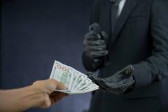 Het geplunderde geld van de zakenmanholding kanonnen van iemand Stock Afbeeldingen