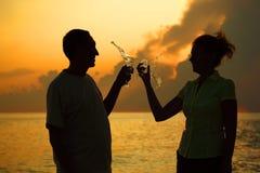 Het gerinkelglazen van het paar. Plonsen van wijn. Stock Foto