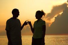 Het gerinkelglazen van het paar. Silhouetten tegen overzees. Royalty-vrije Stock Foto's