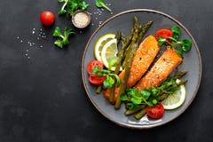 Het geroosterde lapje vlees, de asperge, de tomaat en de maïssalade van zalmvissen op plaat Gezonde schotel voor lunch stock fotografie