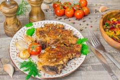 Het geroosterde vlees, tomaten, peper, uien sneed groenten op een witte schotel scherpe Raad met vork en mes, kruiden royalty-vrije stock afbeeldingen