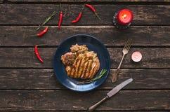 Het geroosterde vlees van Turkije op de blauwe plaat met rode Spaanse peperpeper rond en brandende kaarsen De lapje vleesvlakte l Royalty-vrije Stock Foto