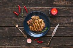 Het geroosterde vlees van Turkije op de blauwe plaat met rode Spaanse peperpeper rond en twee brandende kaarsen De lapje vleesvla Stock Fotografie