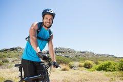 Het geschikte fietser berijden in het platteland die bij camera glimlachen Stock Foto's