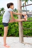 Het geschikte geschiktheidsvrouw uitrekken zich oefent in openlucht uit Stock Foto
