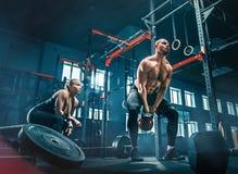 Het geschikte jonge mens het opheffen barbells uitwerken in een gymnastiek stock fotografie