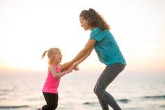 Het geschikte jonge moeder en dochter spelen op het strand bij zonsondergang Stock Afbeeldingen