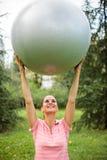 Het geschikte jonge vrouw uitoefenen, die geschiktheidsbal houden boven haar hoofd hoog stock afbeelding